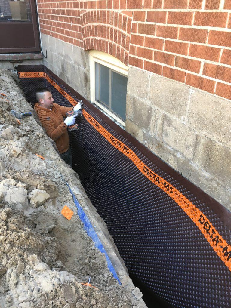 Installing Basement waterproofing membrane